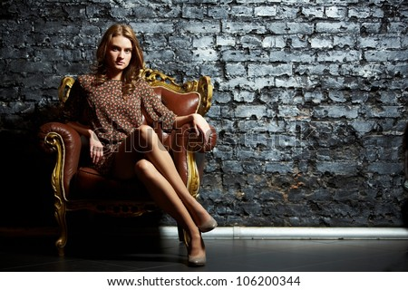 Gorgeous girl sitting in a vintage chair presenting the contrast of high fashion and grunge