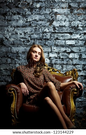 Gorgeous girl sitting in a vintage chair presenting the contrast of high fashion and grunge - stock photo