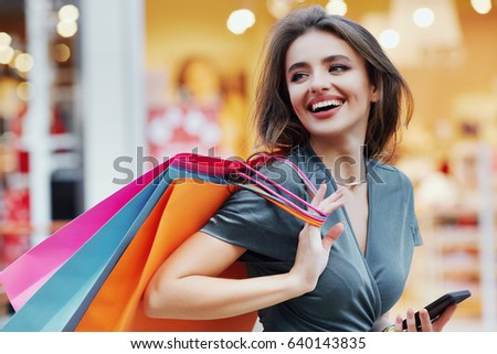Gorgeous girl wearing dress standing with colorful shopping bags and mobile phone, shopping concept, portrait, smiling, close up.