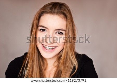 Gorgeous girl with braces smiling cheerfully - stock photo