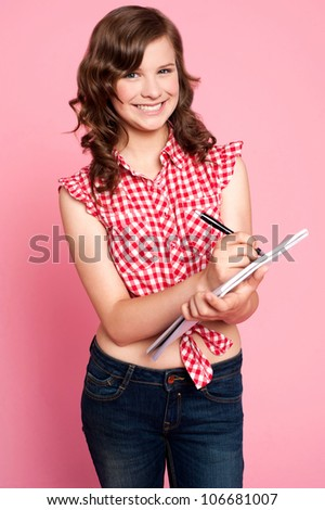 Gorgeous girl writing on notepad while looking at you