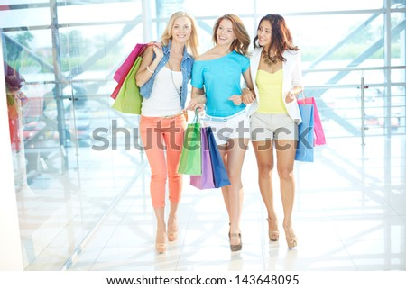 Gorgeous girlfriends with paperbags walking down trade center - stock photo