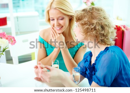 Gorgeous girls looking at engagement ring on the finger of one of them - stock photo