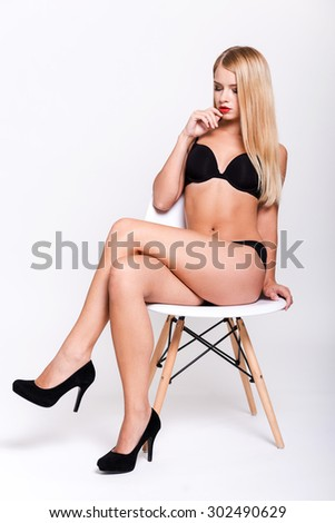 Gorgeous goddess. Attractive young woman in black bra lingerie and high heeled shoes touching her face while sitting at the chair and against white background - stock photo
