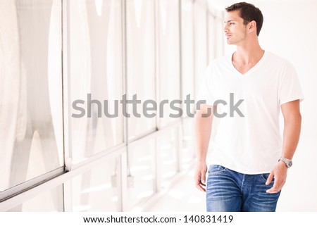 Gorgeous Guy walking and looking out the window in a Penthouse - stock photo