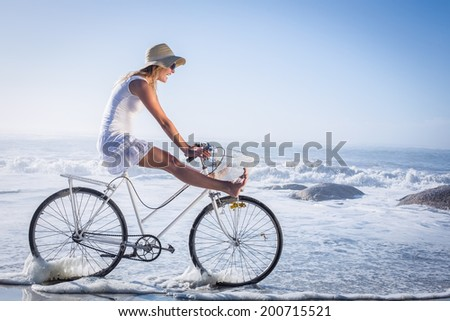 Gorgeous happy blonde on a bike ride at the beach on a sunny day - stock photo