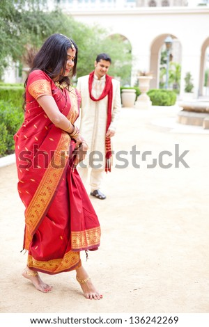 Gorgeous Indian bride dancing as her husband looks on - stock photo
