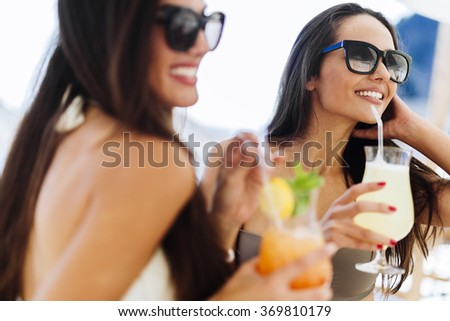 Gorgeous ladies drinking cocktails on beach - stock photo