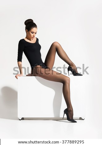 Gorgeous lady being in provocative pose while sitting on cube and wearing alluring underwear and hosiery over isolated background. - stock photo