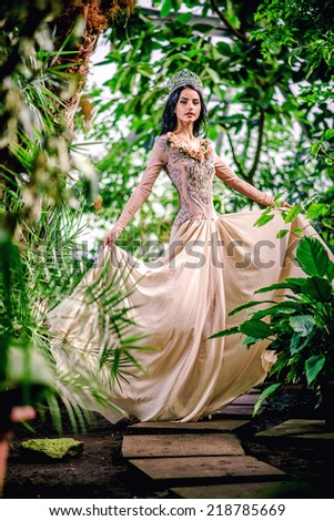 Gorgeous lady in evening dress and with tiara on a head posing in a forest - stock photo