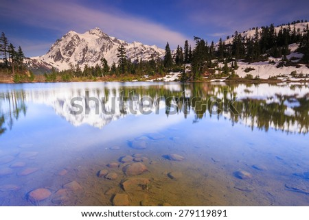Gorgeous landscape of clear water and mountains with dramatic blue sky - stock photo
