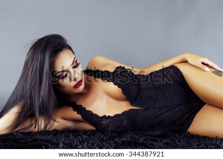 Gorgeous latin young woman posing on the floor over gray background, studio shot - stock photo