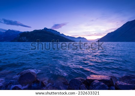 Gorgeous light and color after sunset. Panorama mountain range and sky with clouds reflected in surface of lake. - stock photo