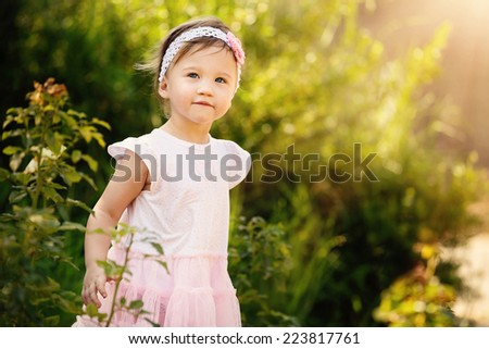 Gorgeous little girl outdoors in green garden  - stock photo