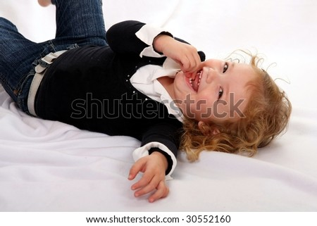 Gorgeous little girl with big smile lying on her back