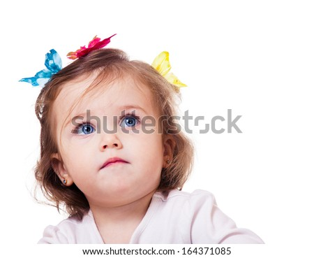 Gorgeous little girl with butterfly clips on head looks up, isolated
