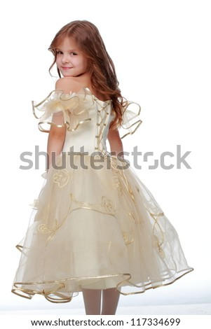 Gorgeous little happy girl is smiling in beautiful dress isolated over a white background