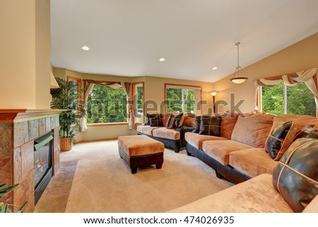Gorgeous living room interior with beige velvet and leather sofa set, ottoman and fireplace. Northwest, USA