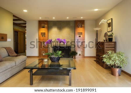 Gorgeous living room with wooden floor, flowers, fire place and beautiful cherry wood cabinetry. - stock photo