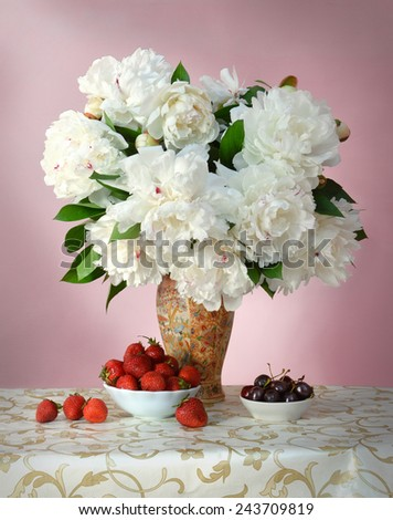 Gorgeous lush white peonies with green leaves in porcelain vase with Chinese painting on openwork tablecloth with golden pattern and dishes with sweet red strawberries and juicy dark burgundy cherries - stock photo