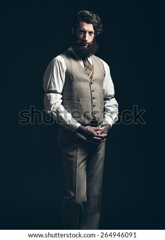 Gorgeous Man with Goatee Beard, Wearing Formal Fashion with Vest, Staring at the Camera While Standing In Front of a Black Background. - stock photo