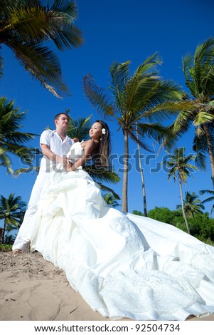 Gorgeous mixed race newlyweds on the beach - stock photo