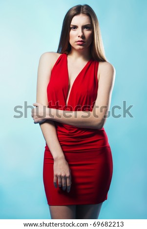 Gorgeous model in elegant red gown, blue background - stock photo