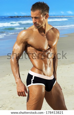 Gorgeous muscular young man at beach - stock photo