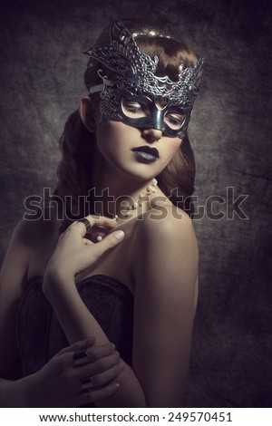 Gorgeous, mysterious female in carnival, silver mask, with brown long hair and dark make up wearing black dress. - stock photo