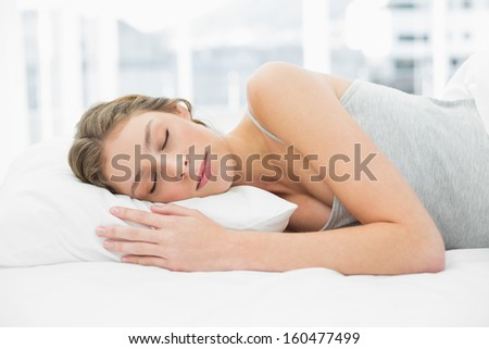 Gorgeous napping woman lying in her bed under the cover in her bedroom