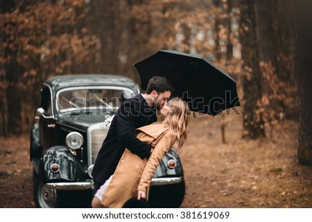 Gorgeous newlywed bride and groom posing in pine forest near retro car in their wedding day