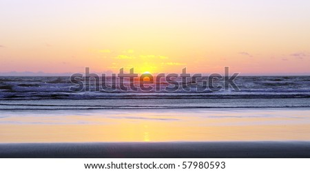 Gorgeous ocean sunset with yellow, purple and pink colors glowing on ocean waves and sandy beach - stock photo