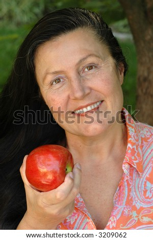 Gorgeous older woman sitting in her garden and enjoying an apple.  Part of the senior healthy lifestyle concept. - stock photo
