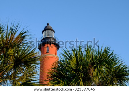 Gorgeous Palm Trees surround the Ponce Inlet Lighthouse in Florida on a perfect sunrise - stock photo