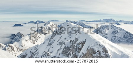 Gorgeous panorama from the the top of  Mt. Stol  (2236 m) in the Karavanke Alps. Mountain peaks are in the bright sun while valleys are covered by fog. Several filters are applied for retro effect.  - stock photo
