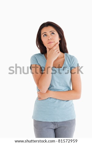Gorgeous pensive woman standing against a white background - stock photo