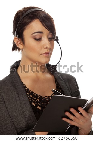 Gorgeous personal assistant with wireless telephone headset making notes in a black notebook. - stock photo