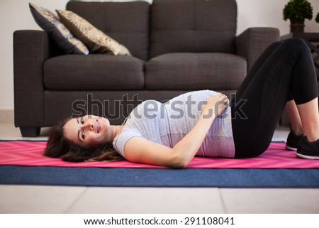 Gorgeous Pregnant Brunette Lying On An Exercise Mat In The Living Room And Smiling