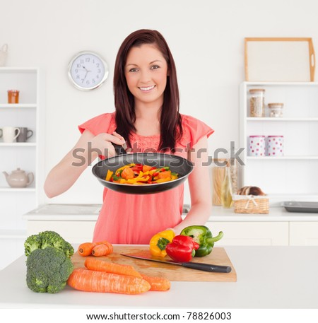 Gorgeous red-haired woman cooking vegetables in the kitchen in her apartment - stock photo