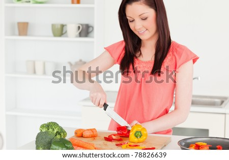 Gorgeous red-haired woman cutting some carrots in the kitchen in her apartment