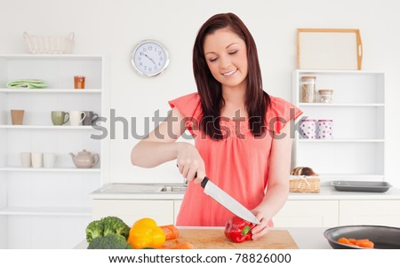 Gorgeous red-haired woman cutting some vegetables in the kitchen in her apartment