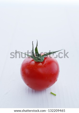 Gorgeous red tomato with stem, shallow depth of field shot against white. - stock photo