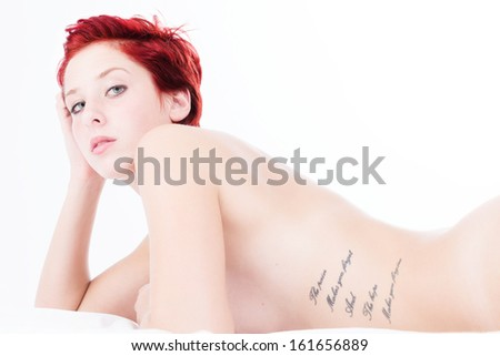 gorgeous redhead young naked woman with a tattoo on bed on white background - stock photo