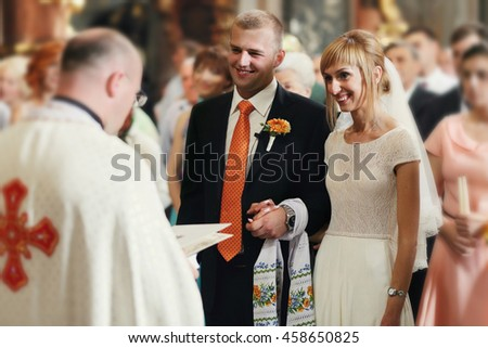 gorgeous romantic happy bride and groom having wedding ceremony on the background of old church