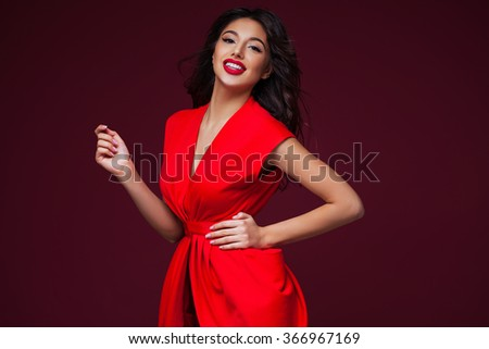 Gorgeous romantic lady in red dress over burgundy background.