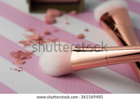 Gorgeous rose gold makeup brushes with pink blush - stock photo