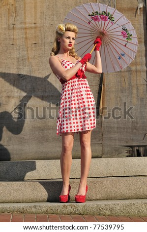 gorgeous 1940's beauty standing with an umbrella - stock photo