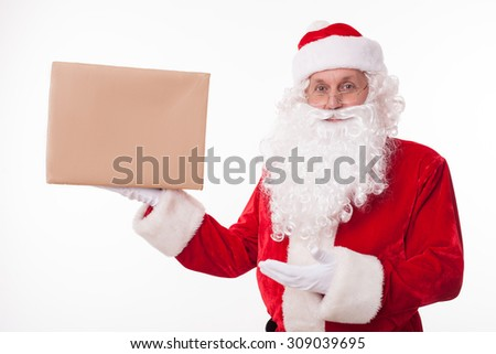 Gorgeous Santa Claus is standing and holding a box of preset. He is presenting it with another hand. The man is looking forward and smiling - stock photo