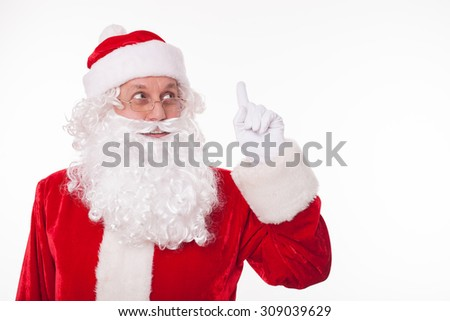 Gorgeous Santa Claus is standing and smiling. He is raising his finger up and looking up thoughtfully. The man remembers everyone. Isolated on background and copy space in right side - stock photo