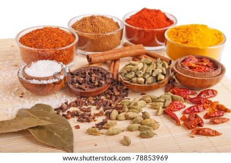 gorgeous setting with cooking spices and herbs (bay leaves, chili powder, cloves, cardamom pods, cinnamon sticks, garam masala, paprika, piri piri, salt, turmeric) on a wooden mat (isolated on white) - stock photo